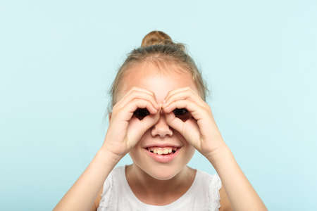 funny ludicrous joyful comic playful girl pretending to look through binoculars made of hands. portrait of a child on blue background. emotion facial expression concept