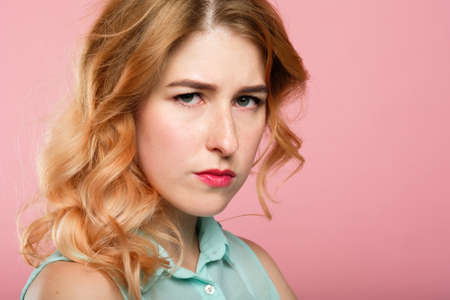 stern piercing look. portrait of a young serious fierce woman. emotional facial expression. beautiful cross girl on pink background.