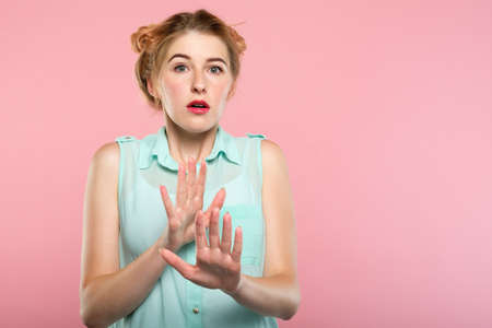 no, stop it. startled nervous scared woman doesnt want to have anything to do with you. rejection refusal. girl putting hands forward protecting herself. portrait on pink background.