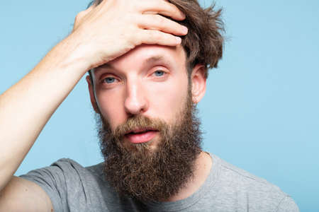 tired exhausted bearded man clutching his forehead. fatigue overworking headache and lack of stamina concept. portrait of a young hipster guy on blue background.