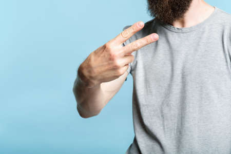 bearded man showing number two or victory sign with his hand. cropped shot of a male torso on blue background. casual hipster in grey t-shirt v-sign or piece gesture. Stock Photo