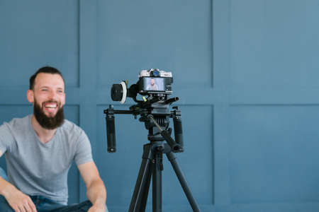 content creation for social media. bearded man shooting video of himself using camera on tripod. modern technology and blogging freelance work concept.