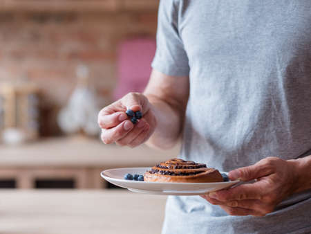 healthy food and eating habits. balanced nutrition and fruit vitamin consumption. unrecognizable man holding a plate with a bun and fresh blueberries.