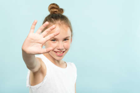 girl covering face from view. private life and paparazzi concept. shutting out refusal and denial. child putting hand forward hiding. portrait of young child on blue background.