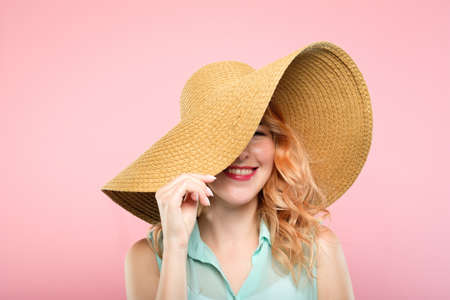 summer vacation tours concept. young pretty woman in a big sunhat ready to go to the beach. cute stylish girl portrait on pink background.