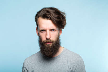 serious frowning man with a troubled look and gathered brows. emotion and feelings concept. portrait of grumpy bearded guy on blue background.