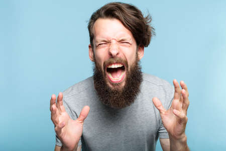 emotional breakdown. angry enraged infuriated crazy man screaming. portrait of a young bearded guy on blue background. emotion facial expression. feelings and people reaction.