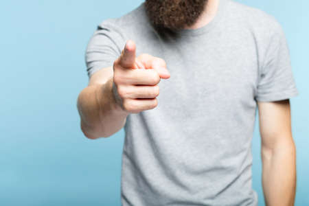 bearded man pointing finger at viewer. indicating gesture. cropped shot of a male torso on blue background. casual hipster in grey t-shirt.