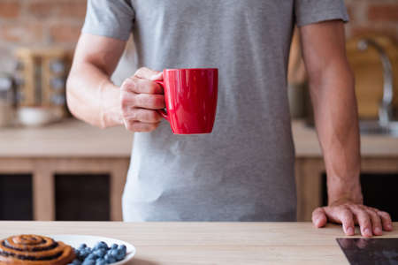 morning tea or coffee. bad breakfast habits. lack of substantial meal. man holding a red mug standing in the kitchen. Stok Fotoğraf