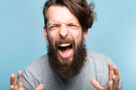 anger and fury. emotional breakdown. enraged man screaming. portrait of a young bearded guy on blue background. facial expression and feelings concept. Reklamní fotografie
