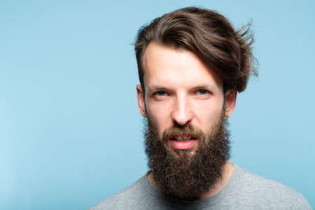 man with a scornful disdainful arrogant look. portrait of a haughty young bearded guy on blue background. emotion facial expression. feelings and people reaction concept.