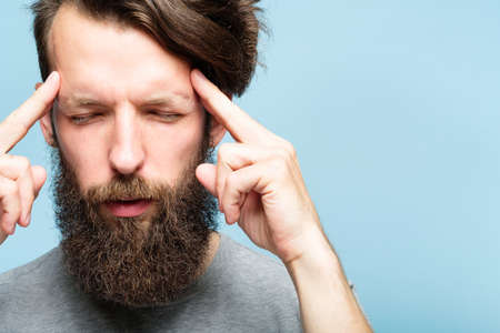 headache fatigue and emotional stress. man holding his head in hands massaging temples. portrait of a young bearded guy on blue background. facial expression and feelings concept. Imagens