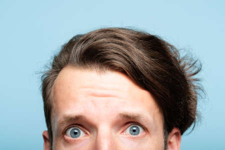 worried nervous man with alarmed look peeping out from the bottom of blue background. emotion and facial expression concept. 写真素材 - 108424500