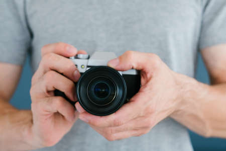 modern technology for photo and video content creation. unrecognizable man holding camera in hands. blogging equipment and tools concept. Stock Photo