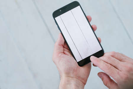 blogger taking photos of white wooden background. social media influencer creating content for channel. hands holding smartphone. mobile photography concept