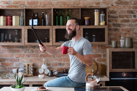 modern technology for photo and video shooting. blogger streaming live video using mobile phone camera and selfie stick. bearded hipster man communicating with subscribers from his kitchen.