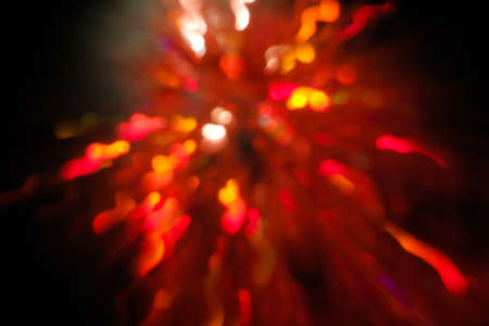 abstract lens flare on black background. red defocused bokeh lights. blurred christmas sparkler wallpaper decor. festive glowing new year firework design.