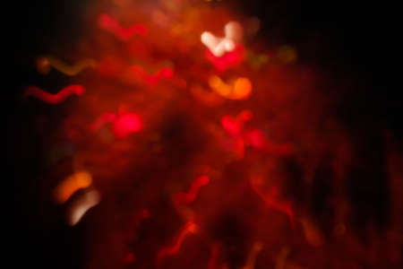 abstract lens flare on black background. red defocused bokeh lights. blurred christmas wallpaper decor. festive glowing christmas sparkler design.