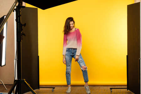 modeling job lifestyle. backstage photoshoot. young girl posing. art and hobby concept. casual young beautiful brown haired woman in ripped jeans on yellow background.