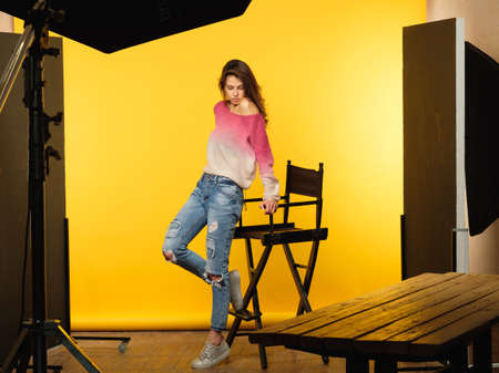 backstage photography. model posing during photoshoot. art and hobby concept. casual young beautiful brown haired girl in ripped jeans on yellow background. 스톡 콘텐츠