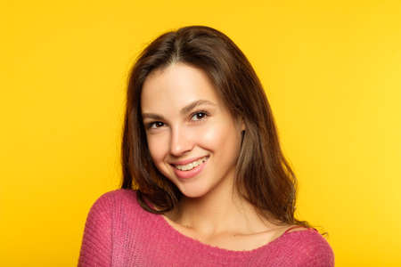 emotion face. smiling woman pleased with herself. self-satisfied young beautiful brown haired girl. portrait on yellow background. Stock Photo - 108722879