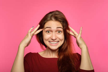 emotion face. amazed happy smiling surprised joyful jolly amused woman. young beautiful brown haired girl portrait on pink background. Zdjęcie Seryjne