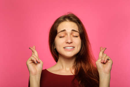 woman keeping fingers crossed. plead and hope for luck concept. young girl portrait on pink background. emotional facial expression.