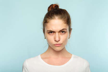 emotion face. frowning grumpy woman with pursed lips and piercing glance. young beautiful brown haired girl portrait on blue background.