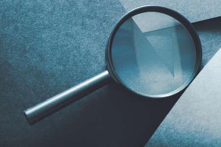 Lupe. Vergleich Bewertung und Analyse. Lupe auf geschichtetem blauem Papierhintergrund.
