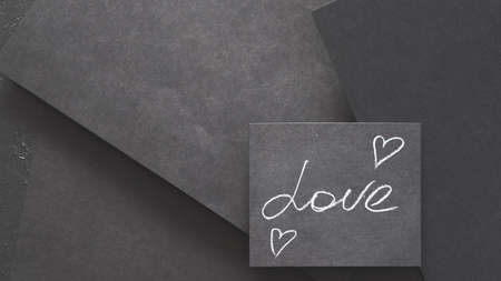 love and hearts. feelings and romance. chalk writing on black layered paper background with copy space.