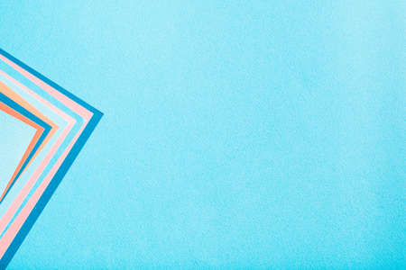construction paper texture background. blue backdrop with colorful geometric accent sheets. copyspace concept.
