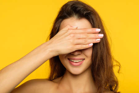 see no evil concept. young woman covering her eyes with hand ignoring or disregarding something. female portrait on yellow background.