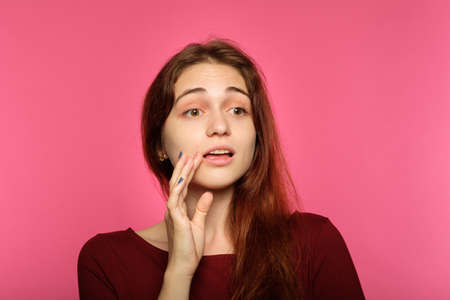 surprised shocked girl. young beautiful woman with brown hair on pink background. emotional facial expression.