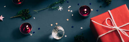 festive holiday decor. christmas background for landing page. red present candles and decorative elements on blue backdrop. 写真素材