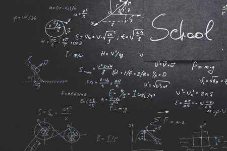 school exams and test in physics. education and learning. chalkboard inscribed with formula and equation.