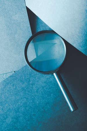 Lupe. Forschungs- und Untersuchungskonzept für die wissenschaftliche Forschung. Lupe auf geschichtetem blauem Papierhintergrund.