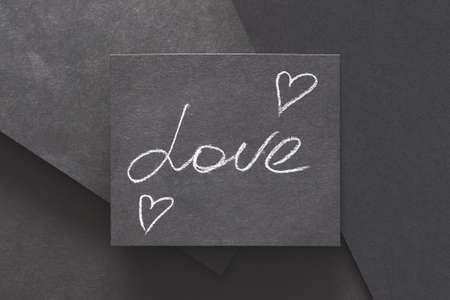 love and hearts. romance happiness and emotion. message handwritten on black layered paper background.