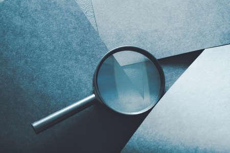 vergrootglas. dingen vinden of problemen opsporen concept. loep op gelaagde blauw papier achtergrond.