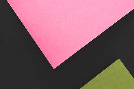 abstract geometric background. pink and green paper on black backdrop. empty space concept.
