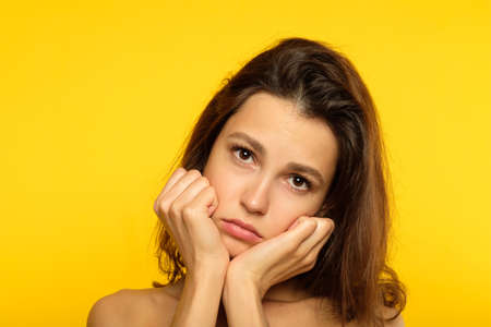 emotion face. sad depressed downcast gloomy low spirited woman. young beautiful brunette girl portrait on yellow background. Stockfoto