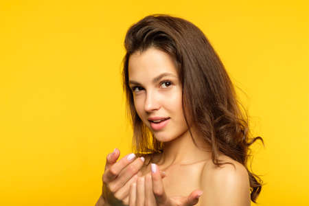 seductress and heartbreaker. attractive beautiful young woman pulling you closer or inviting. alluring and provocative portrait of a girl on yellow background.