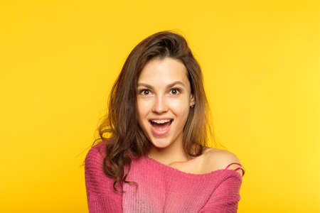 surprised shocked girl. young beautiful woman with brown hair on yellow background. emotional facial expression.