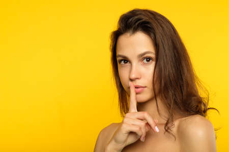 girl keeping her secret. woman is a mystery worth solving. young beautiful female portrait on yellow background. finger on lips. Stock Photo