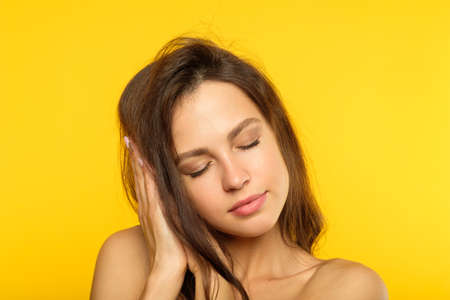 sweet dreams. content calm beautiful young woman pretending to be sleeping on the pillow made of her hands. beautiful brown haired girl on yellow background. 版權商用圖片