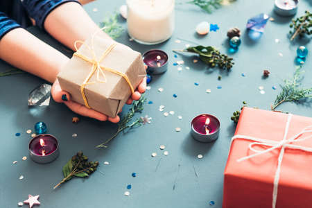 christmas presents giving tradition. hands holding craft gift package against blue decorated background. holiday spirit and seasonal embellishments concept. Stock Photo