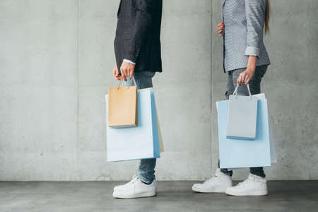 shopping lifestyle and buying addiction. midsection of man and woman holding multiple bags in hands. Stock Photo