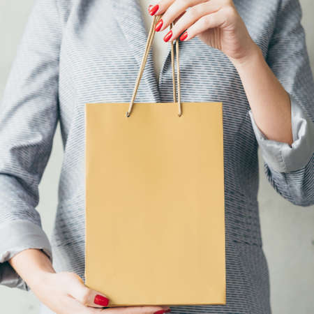 brown paper bag in woman hands. gift shopping and store discounts concept. 스톡 콘텐츠