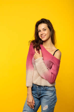emotion and feelings expression. smiling woman pleased with herself. happy content young beautiful brown haired girl. portrait on yellow background.