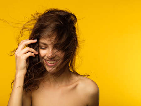 haircare and styling. beauty and health. quality shampoo and conditioner or hair salon advertisement concept. brunette girl with wavy messy locks on yellow background.