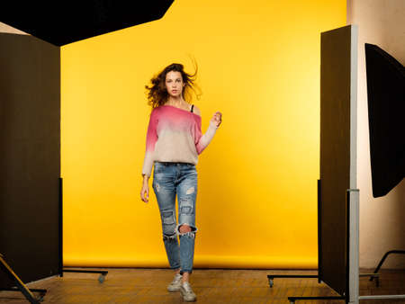 backstage photography. photoshoot workspace. creative hobby and art concept. casual young beautiful brown haired female model in ripped jeans on yellow background.